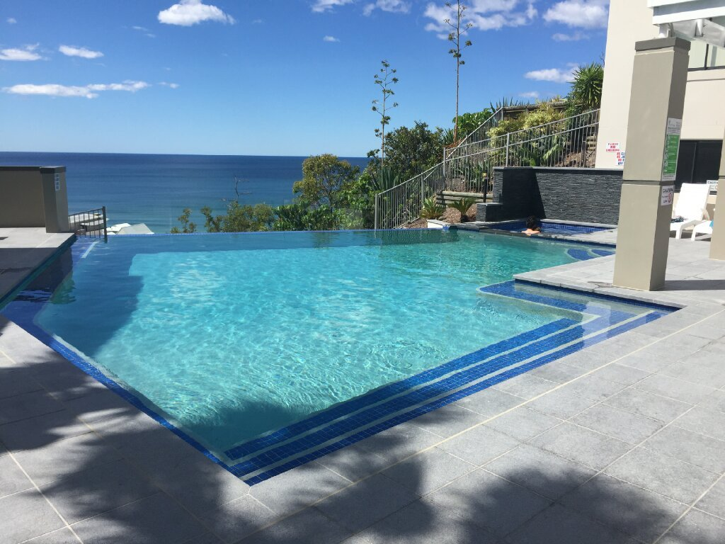 This is an infinity edge swimming pool at Magic Mountain that our team of pool builders on the Gold Coast renovated and bought back to life with a modern finish.