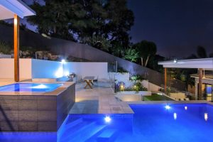 Gold Coast pool builders have built this custom designed pool with spa, unique pool lighting, and landscaped surrounds.
